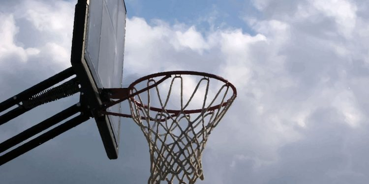 A basketball net in cloudy sunshine.
